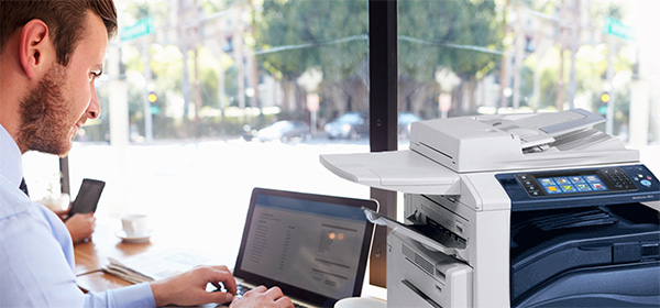 Homem configurando uma impressora multifunções