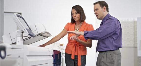 Duas pessoas na manutenção preventiva de uma impressora multifunções