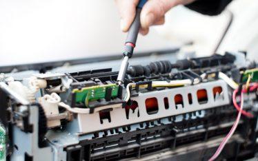 Homem a concertar maquinas fotocopiadoras